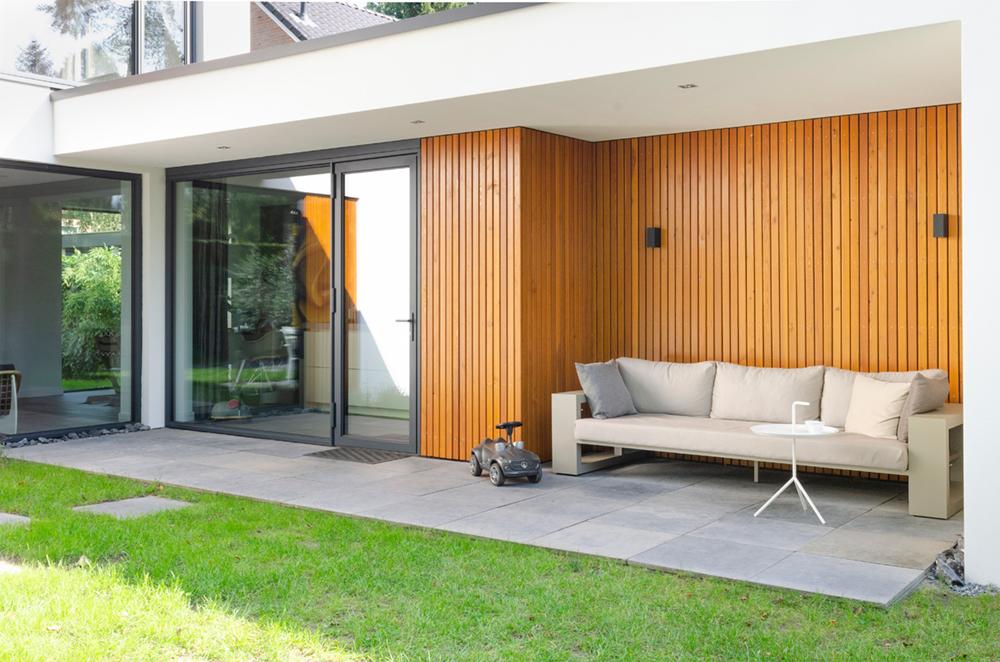 Resultaat verbouwing bungalow tot villa - bank onder afdak in tuin
